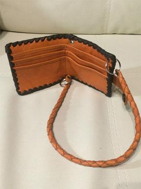49. Рыжий кошелёк с тёмно-коричневой оплёткой и плетёным кожаным шнурком.